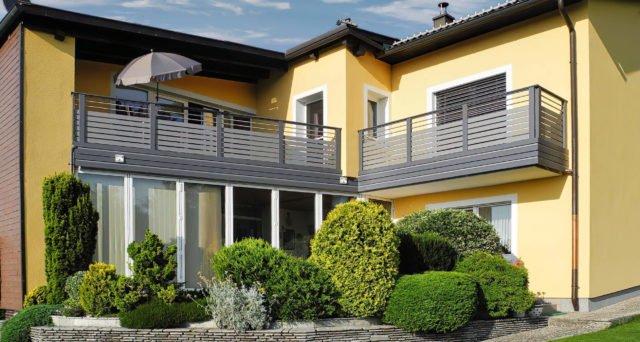 Gepflegter Garten vor gelbem Einfamilienhaus mit Alu Design Madrid Balkon